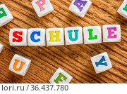 Letter dice on a wooden background - School - Schule German. Стоковое фото, фотограф Zoonar.com/Boris Zerwann / easy Fotostock / Фотобанк Лори