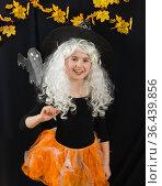 Веселая девочка в белом парике и черно-оранжевом костюме ведьмы на черном фоне. Стоковое фото, фотограф Наталья Гармашева / Фотобанк Лори