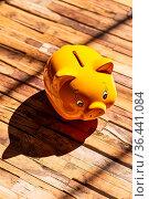 Ein gelbes Sparschwein steht auf einem Holzboden und wirft einen starken... Стоковое фото, фотограф Zoonar.com/ironjohn / easy Fotostock / Фотобанк Лори