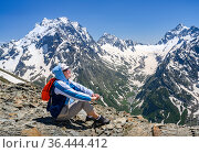 A tourist high in the Dombay Mountains, covered with snow, admires the expanse. Стоковое фото, фотограф Сергей Фролов / Фотобанк Лори