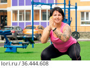 Strong plump woman doing squats on a sports ground in the courtyard of a city house. Стоковое фото, фотограф Евгений Харитонов / Фотобанк Лори