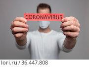 Worried man wearing a respiratory mask, holding the Coronavirus Covid... Стоковое фото, фотограф Zoonar.com/Tomas Anderson / easy Fotostock / Фотобанк Лори