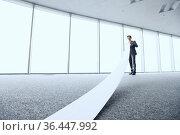 Businessman or male lawyer unrolling and reading long paper list in... Стоковое фото, фотограф Zoonar.com/Tatiana Badaeva / easy Fotostock / Фотобанк Лори