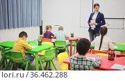 Modern young female teacher controlling learning process at lesson in primary school. Стоковое видео, видеограф Яков Филимонов / Фотобанк Лори