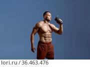 Muscular male athlete drinks water in studio. Стоковое фото, фотограф Tryapitsyn Sergiy / Фотобанк Лори