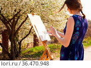Artist paints a picture of blooming cherry tree in the garden. Woman... Стоковое фото, фотограф Zoonar.com/Oksana Shufrych / easy Fotostock / Фотобанк Лори