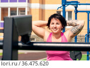 Young woman shakes her back muscles in the city yard using street exercise machine hyper extension bench. Стоковое фото, фотограф Евгений Харитонов / Фотобанк Лори