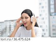 Teen girl enjoying music with headphones outdoors. Стоковое фото, фотограф Евгений Харитонов / Фотобанк Лори
