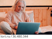 Senior Adult Woman with laptop and mibile headphones relaxing at glamping... Стоковое фото, фотограф Zoonar.com/Max / easy Fotostock / Фотобанк Лори