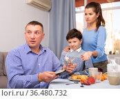 Frustrated man giving money to wife and boy. Стоковое фото, фотограф Яков Филимонов / Фотобанк Лори