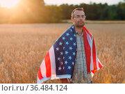 Man farmer covering american flag in wheat field at sunset. Farming... Стоковое фото, фотограф Zoonar.com/Max / easy Fotostock / Фотобанк Лори