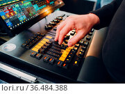 The sound engineer hand moves the sliders on the sound mixing console... Стоковое фото, фотограф Zoonar.com/Max / easy Fotostock / Фотобанк Лори