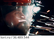 Man welder grinder in transparent protective mask with flying sparks... Стоковое фото, фотограф Zoonar.com/Max / easy Fotostock / Фотобанк Лори