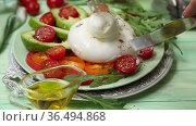 Burrata with tomatoes, arugula, avocado and wine on a green background. Стоковое видео, видеограф Марина Володько / Фотобанк Лори