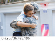 Smiling caucasian male soldier with son outside house holding american flags. Стоковое фото, агентство Wavebreak Media / Фотобанк Лори