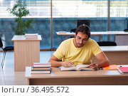 Young male student preparing for exams in the classroom. Стоковое фото, фотограф Elnur / Фотобанк Лори