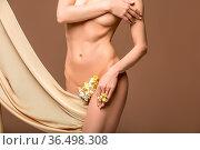 Beautiful naked woman with yellow flowers between legs an silk fabrics... Стоковое фото, фотограф Zoonar.com/Svetlana Mandrikova (@Svetography) / easy Fotostock / Фотобанк Лори