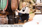 Seller pouring draft wine from wooden barrels. Стоковое фото, фотограф Яков Филимонов / Фотобанк Лори