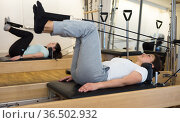 woman pilates stretching sport in reformer bed. Стоковое фото, фотограф Яков Филимонов / Фотобанк Лори