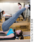 Woman exercising torson rotation at gym using pilates beds. Стоковое фото, фотограф Яков Филимонов / Фотобанк Лори