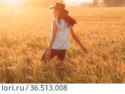 Woman farmer in cowboy hat walking with hands on ears at agricultural... Стоковое фото, фотограф Zoonar.com/Max / easy Fotostock / Фотобанк Лори