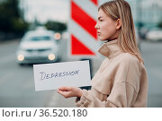 Woman holding white sheet paper labeled word Depression in hand. Стоковое фото, фотограф Zoonar.com/Max / easy Fotostock / Фотобанк Лори