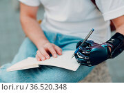 Young disabled man writes in notebook with pen in artificial prosthetic... Стоковое фото, фотограф Zoonar.com/Max / easy Fotostock / Фотобанк Лори