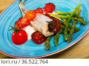 Baked fish poutassou with dried tomatoes, asparagus and creamy-garlic sauce. Стоковое фото, фотограф Яков Филимонов / Фотобанк Лори
