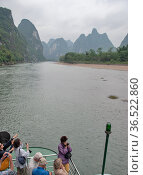 Pleasure ships move along the Li River against the backdrop of picturesque mountains (2010 год). Редакционное фото, фотограф Александр Карпенко / Фотобанк Лори