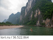 Locals travel along the Li River in a bamboo motorboat (2010 год). Стоковое фото, фотограф Александр Карпенко / Фотобанк Лори