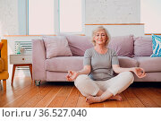 Senior adult smiling woman practicing yoga at home living room. Elderly... Стоковое фото, фотограф Zoonar.com/Max / easy Fotostock / Фотобанк Лори