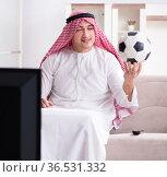 Arab man watching tv at home. Стоковое фото, фотограф Elnur / Фотобанк Лори