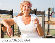 Old lady in outdoor workout station. Стоковое фото, фотограф Татьяна Яцевич / Фотобанк Лори