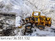 Очистка дороги от снега во дворе жилого дома с помощью грейдера. Москва. Редакционное фото, фотограф Владимир Устенко / Фотобанк Лори