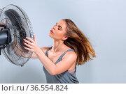 Young woman enjoying cool air wind from electric fan at hot summer... Стоковое фото, фотограф Zoonar.com/Svetlana Radayeva / easy Fotostock / Фотобанк Лори
