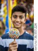 A 12-year-old boy holds a colorful caramel apple covered in sprinkles... Стоковое фото, фотограф Lori Epstein / age Fotostock / Фотобанк Лори