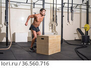 Muscular male athlete is practicing jumping on a wooden box in modern... Стоковое фото, фотограф David Herraez Calzada / easy Fotostock / Фотобанк Лори