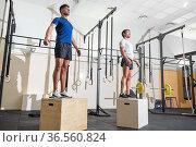 Two man jumping on fit box at gym. High quality photo. Стоковое фото, фотограф David Herraez Calzada / easy Fotostock / Фотобанк Лори