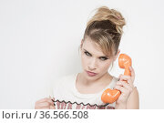 Junge blonde Frau mit naiv nachdenklichem Blick bei einem Telefongespräch... Стоковое фото, фотограф Zoonar.com/Hans Eder / easy Fotostock / Фотобанк Лори
