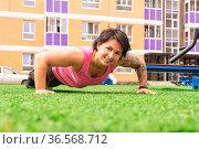 Muscular plump woman doing push-up exercises on the sports ground. Стоковое фото, фотограф Евгений Харитонов / Фотобанк Лори