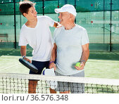 padel players of different generations talking on court playing paddle. Стоковое фото, фотограф Татьяна Яцевич / Фотобанк Лори