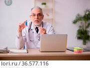 Old doctor in vaccination concept. Стоковое фото, фотограф Zoonar.com/Elnur Amikishiyev / easy Fotostock / Фотобанк Лори