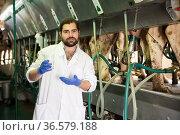 Milkmaid man with fresh milk near automatical cow milking machines. Стоковое фото, фотограф Яков Филимонов / Фотобанк Лори