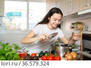 Woman holding cooking ladle spoon while cooking soup. Стоковое фото, фотограф Яков Филимонов / Фотобанк Лори