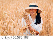 Young Woman in straw hat holding sheaf of wheat ears at agricultural... Стоковое фото, фотограф Zoonar.com/Max / easy Fotostock / Фотобанк Лори