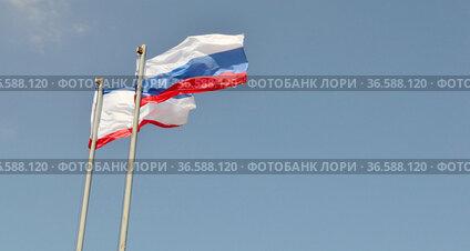 Два флага - Крыма и России развиваются на фоне голубого неба