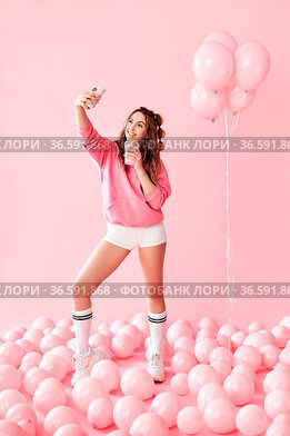 Full length portrait of trendy young woman making selfie photo on...