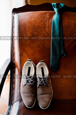 Men's shoes and a tie on a brown leather chair. High quality photo