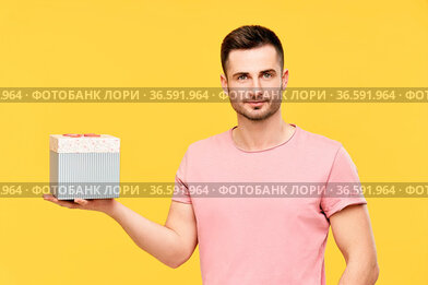 Handsome young man holding gift box on yellow studio background. Celebration...