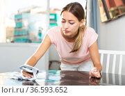 Girl with dishcloth cleaning kitchen table. Стоковое фото, фотограф Яков Филимонов / Фотобанк Лори